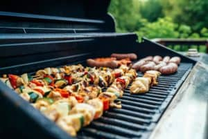 Chicken skewers and sausages being grilled