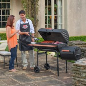 A man and a woman discussing next to a Char-Griller E1224