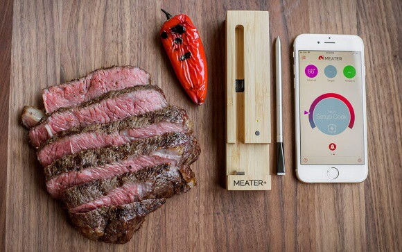 Cut meat and a Meater thermometer on a plank