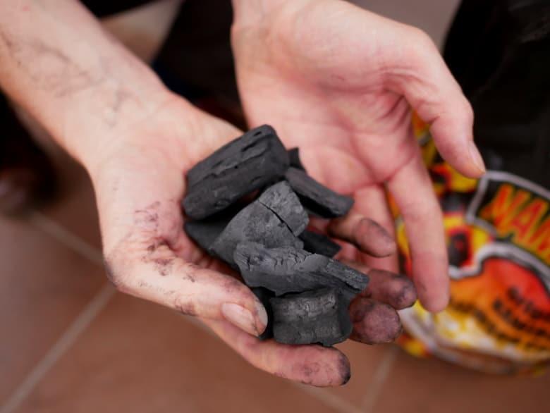 Hands full of charcoal lumps