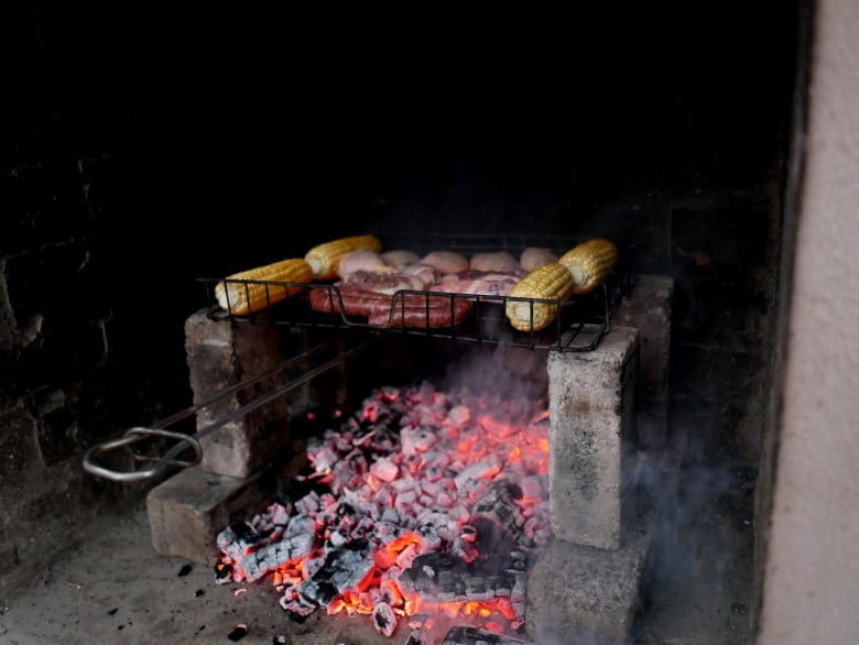 Corn, saussages, and chicken being grilled on charcoal