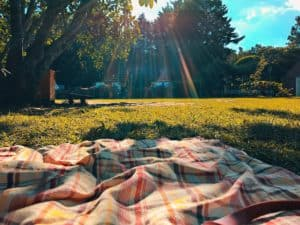 A picnic blanket on the grass before a tailgate party