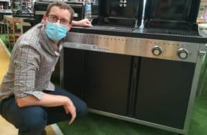 Benoit in front of a gas and charcoal grill combo